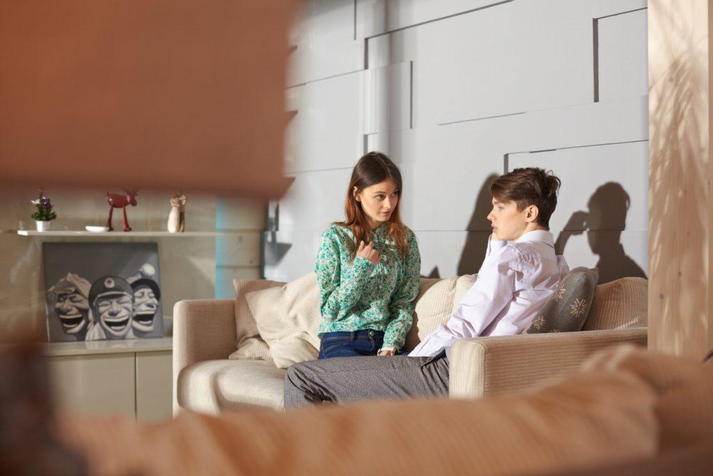 部屋で冷静に話し合いをするカップル