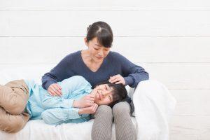 母親の膝枕でニコニコしている男性