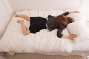 ベッドにうつ伏せで寝そべる女性