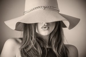 帽子を深くかぶって口元しか見えない女性