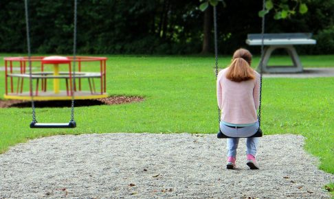 公園のブランコで肩を落とす女性の後ろ姿