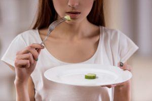 少量の食べ物が乗ったお皿を持っている女性