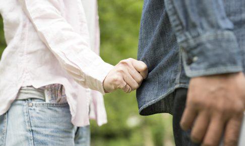 男性の服の裾を掴む女性