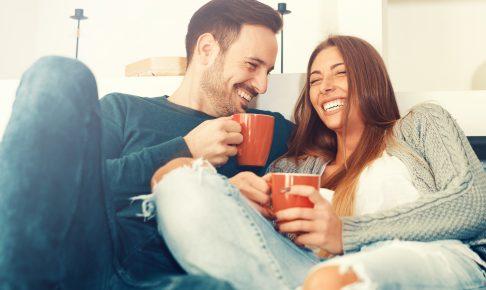 ソファーでくつろぎながら楽しそうな表情のカップル